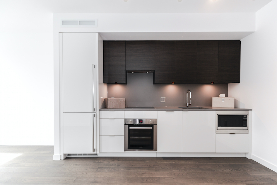 white minimalist kitchen in Olympic Village condo