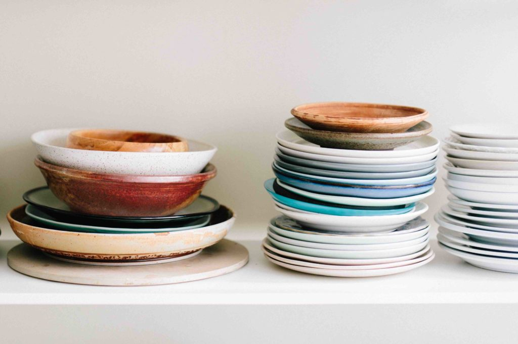 Assortment of rustic plates and bowls stacked on top of each other