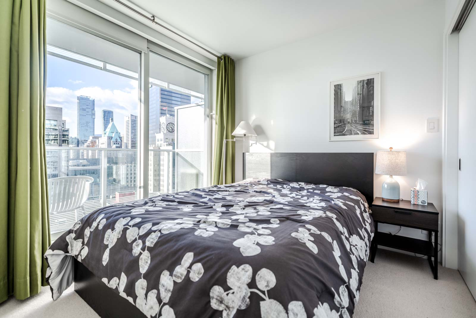 Bedroom with green curtains and black-and-white floral bedspread and view of Downtown Vancouver.