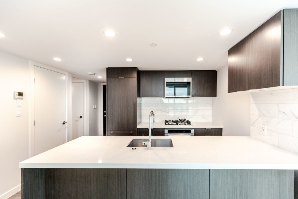 Kitchen with stainless steel appliances and white countertops in Vancouver luxury rental condo.