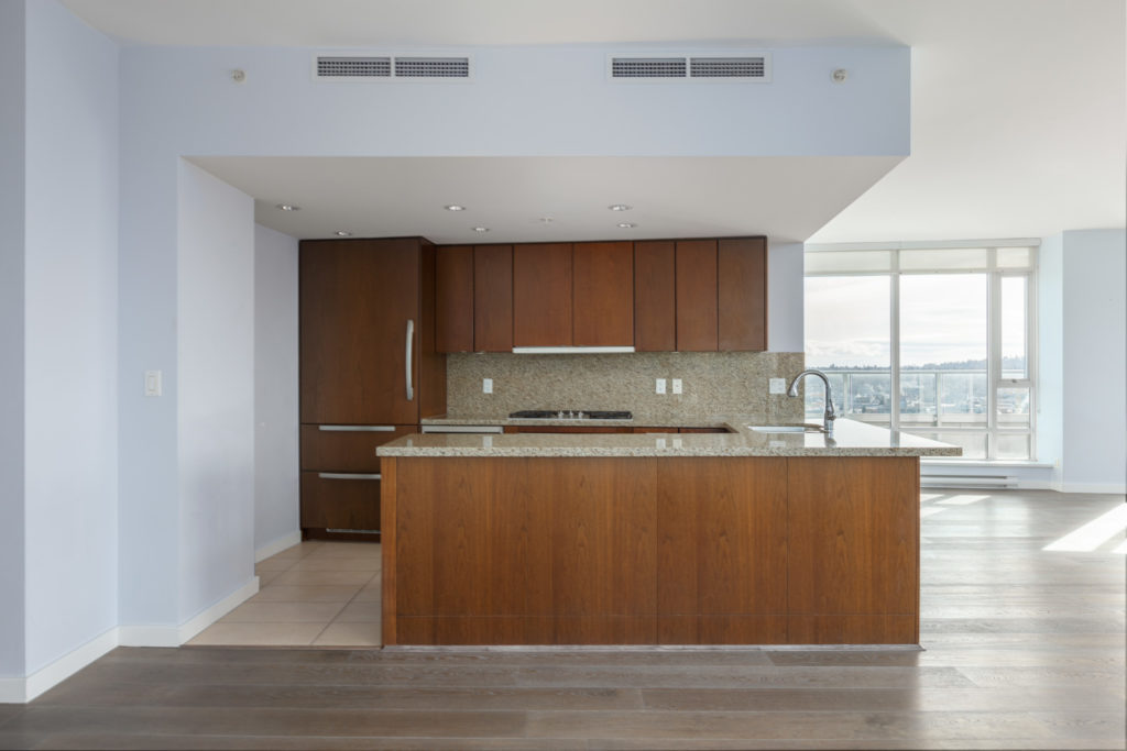 kitchen with wooden cabinets and kitchen island of yaletown penthouse condo at 918 cooperage way