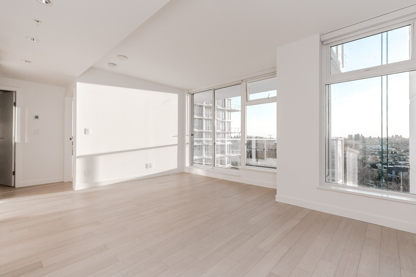 empty living room with white walls and hardwood floors and windows