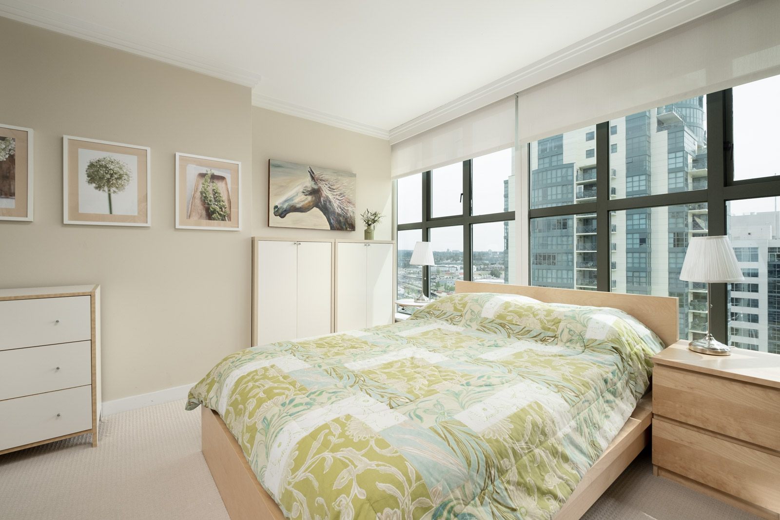 Bedroom inside furnished Downtown Vancouver rental condo with windows offering city views.