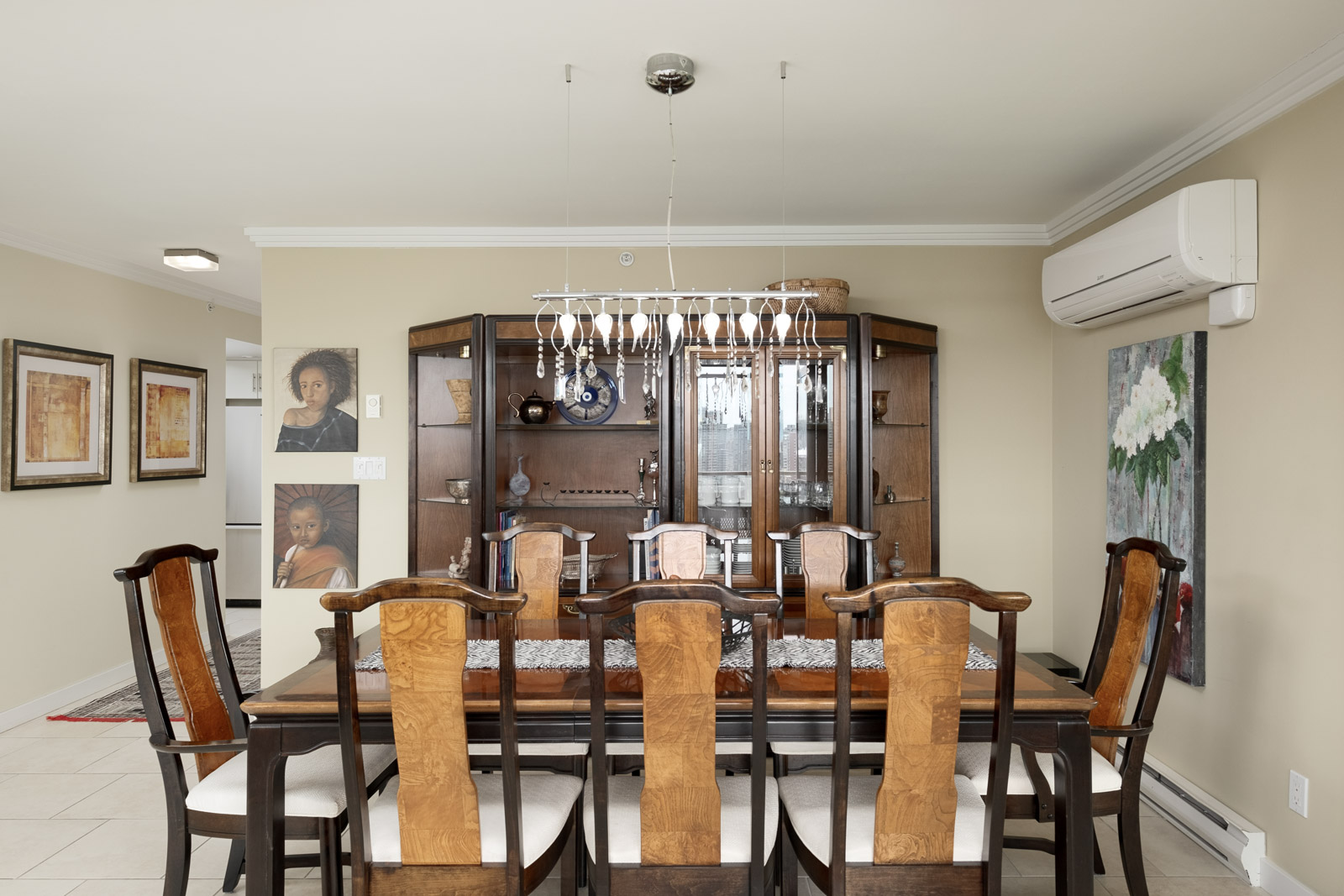 Dining area of furnished Vancouver rental condo with decorative shelving and hanging artwork.