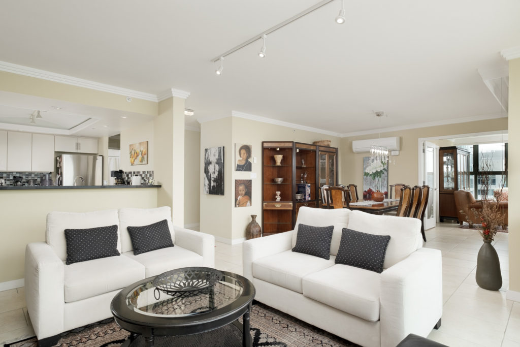 Living area of Vancouver rental with white couches and access to private balcony.