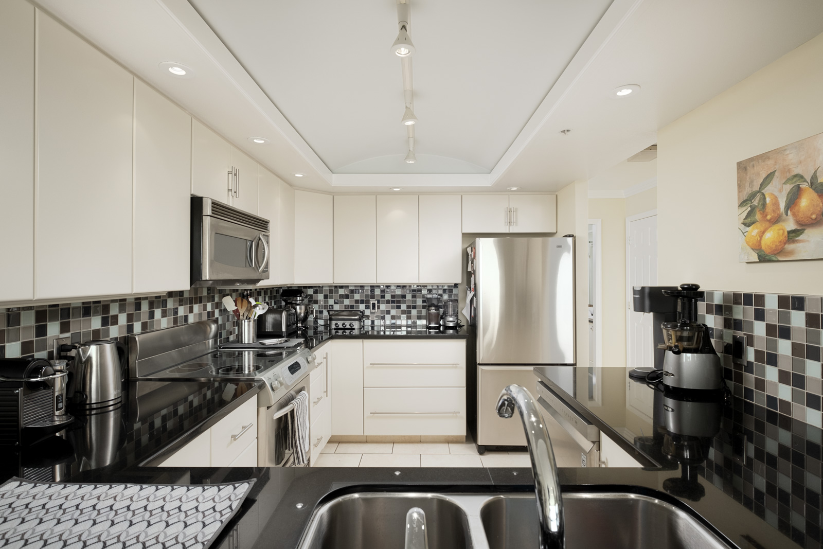 Kitchen with black-and-white tiling scheme and stainless steel appliances inside furnished Vancouver rental condo.