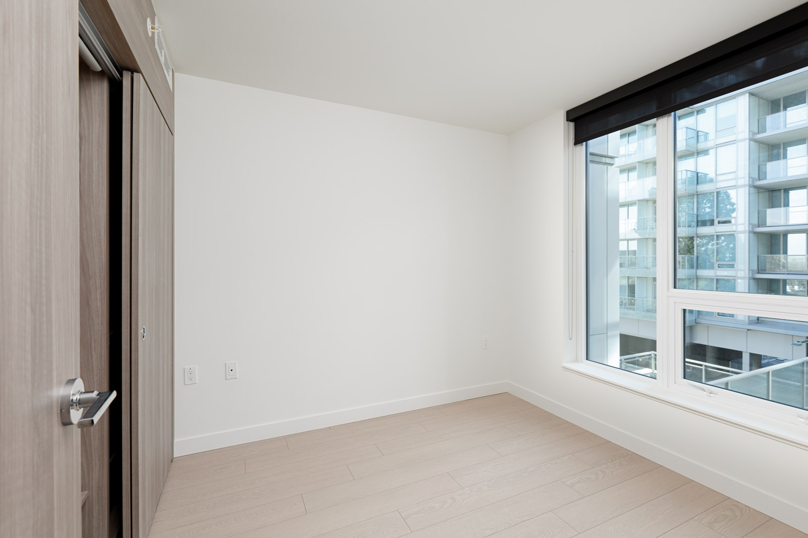 Bedroom with view and ash flooring at Vancouver condo rental.