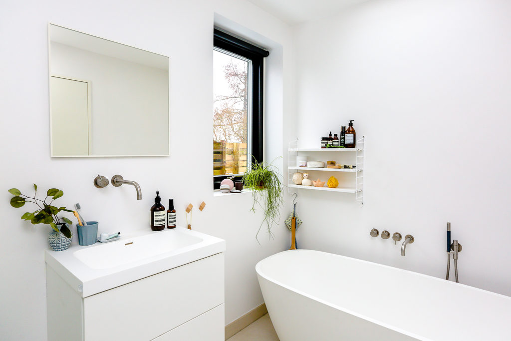 White bathroom featuring large tub and Aesop products