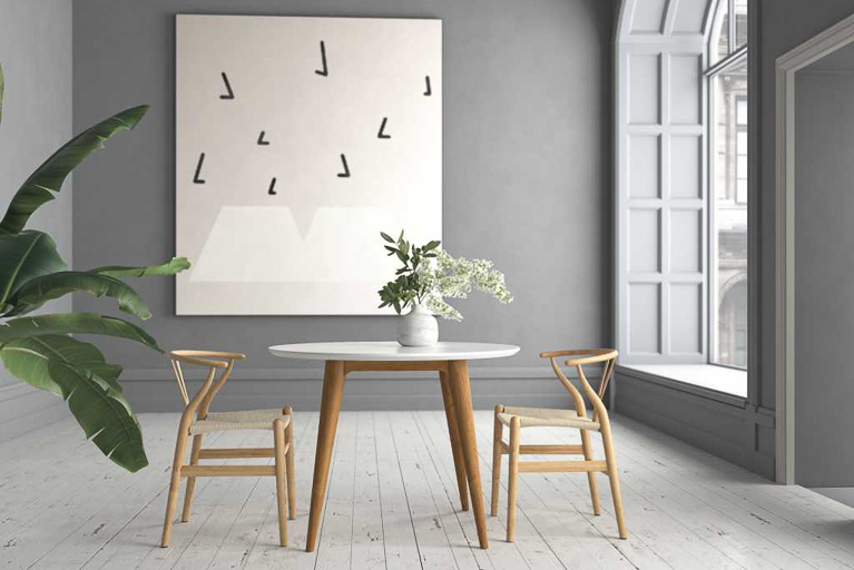 Mid-century modern table and chairs with black-and-white artwork and plant in background