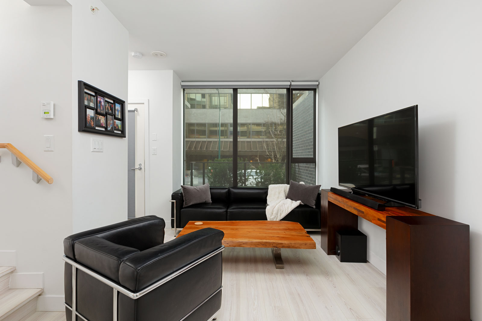 Living area with black leather seating and view at Downtown Vancouver condo rental.