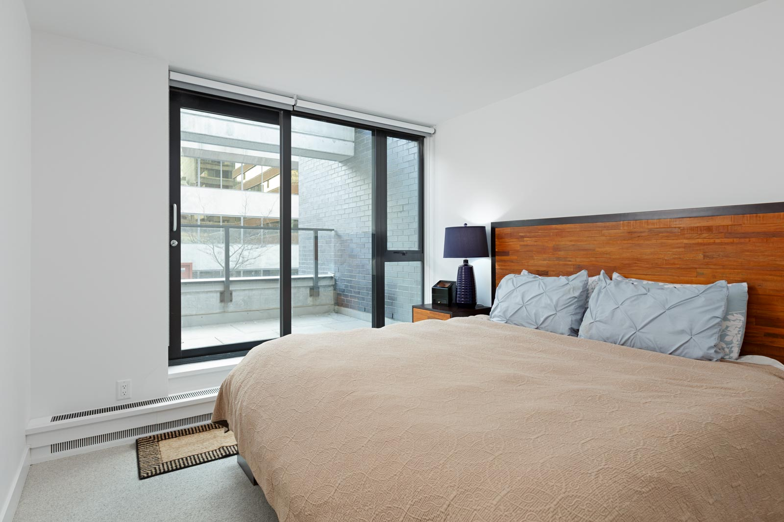 Bedroom with black window frames and access to balcony at Downtown Vancouver rental condo.