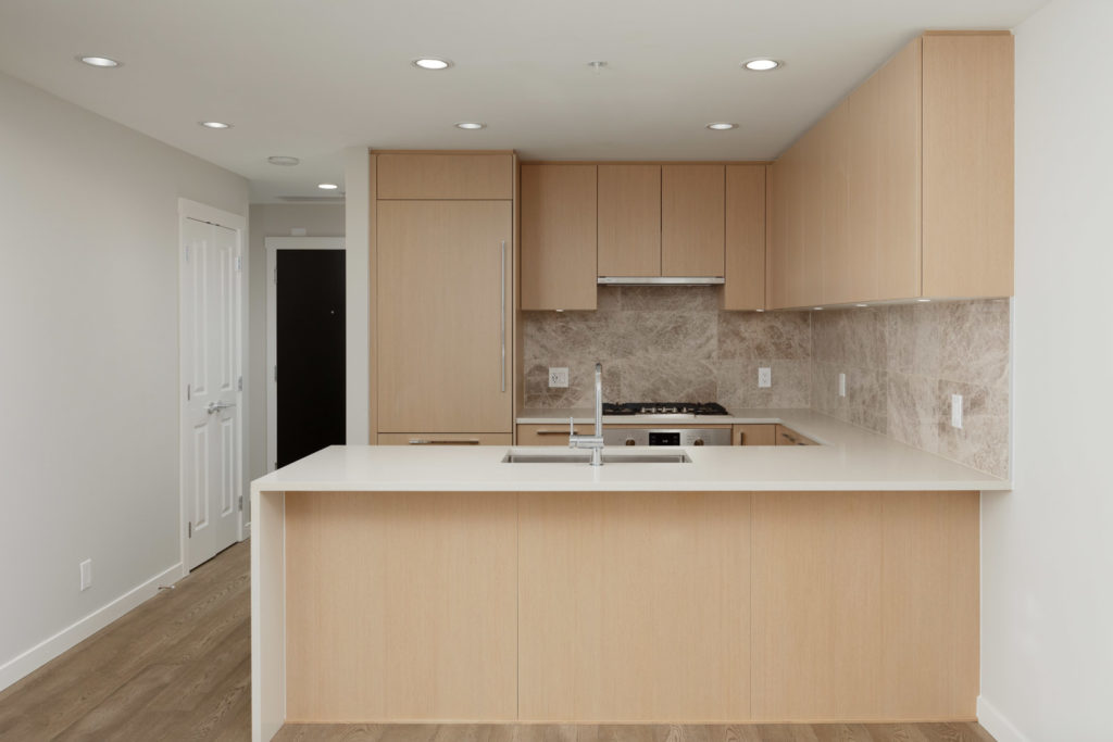 Newly renovated kitchen with oak cabinetry inside UBC rental condo.