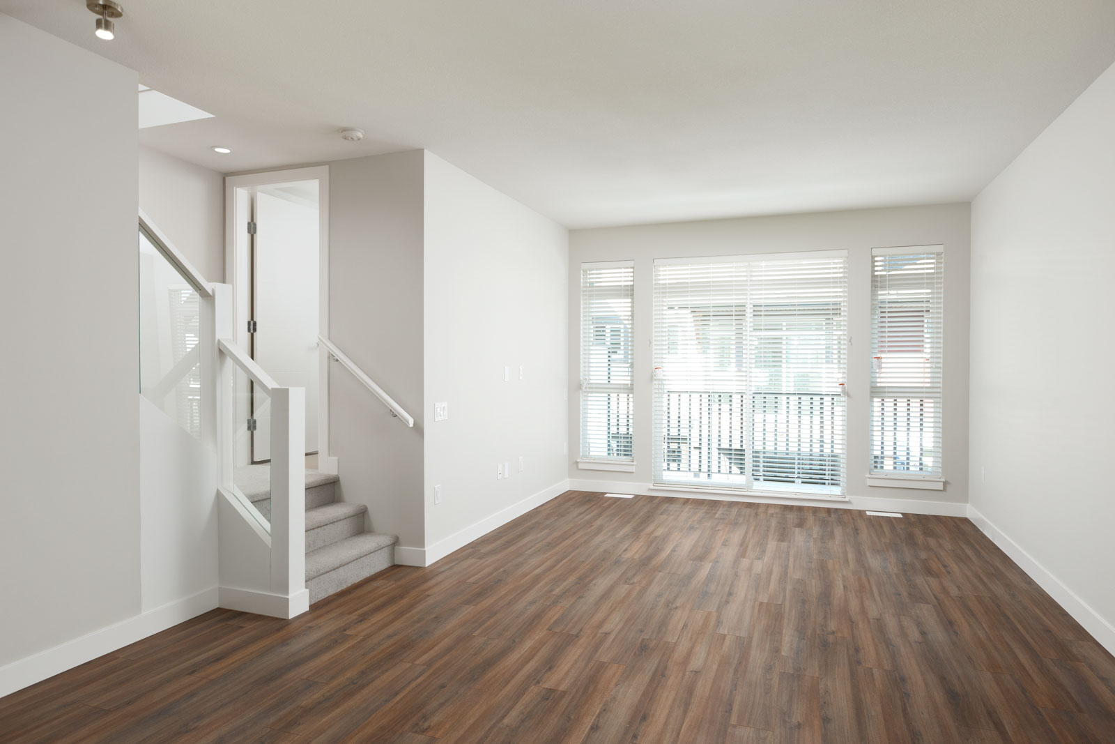 Living area with access to private balcony in Richmond rental townhome.