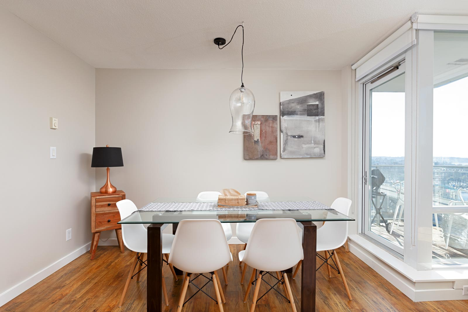 Dining area with glass top table and white chairs in Yaletown Vancouver condo with view.