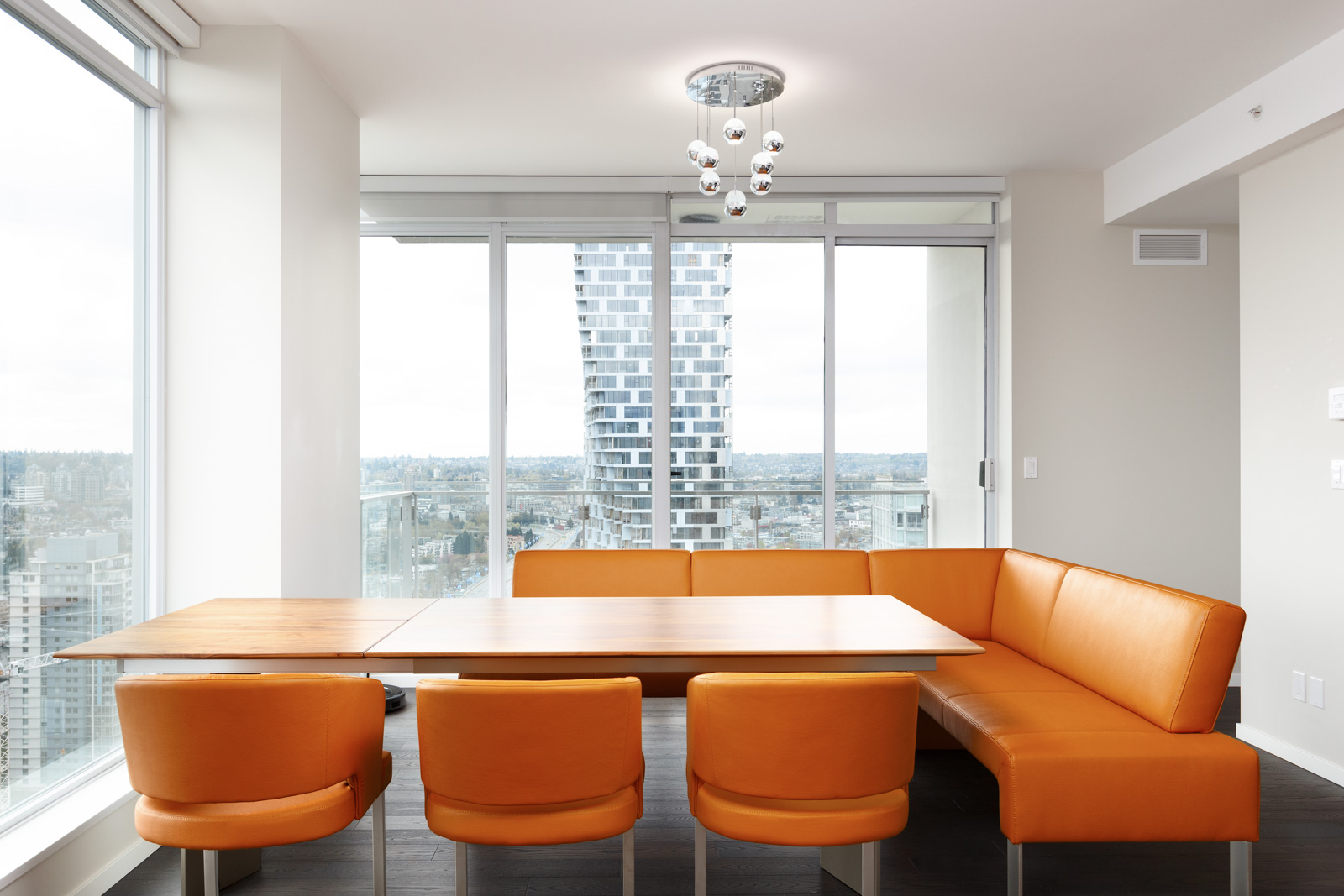 Orange themed dining area with view of Vancouver in rental condo.