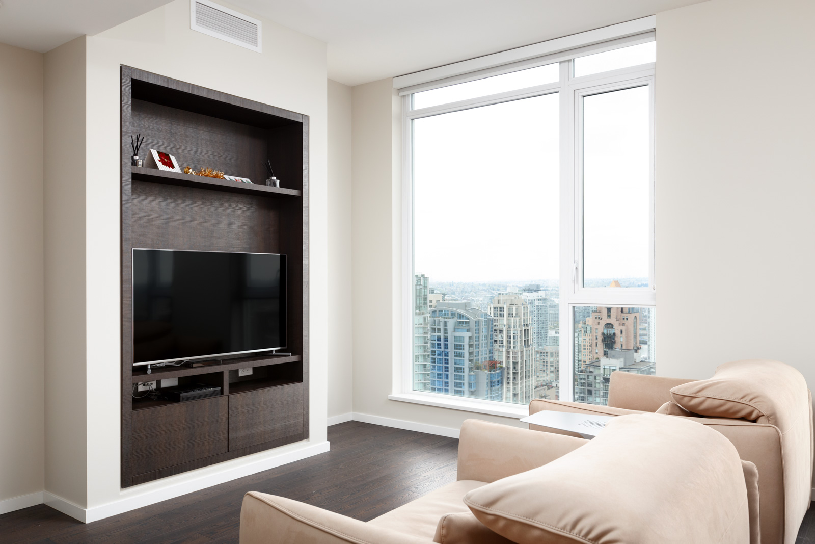 Living area with dark wood entertainment unit in Vancouver rental condo.