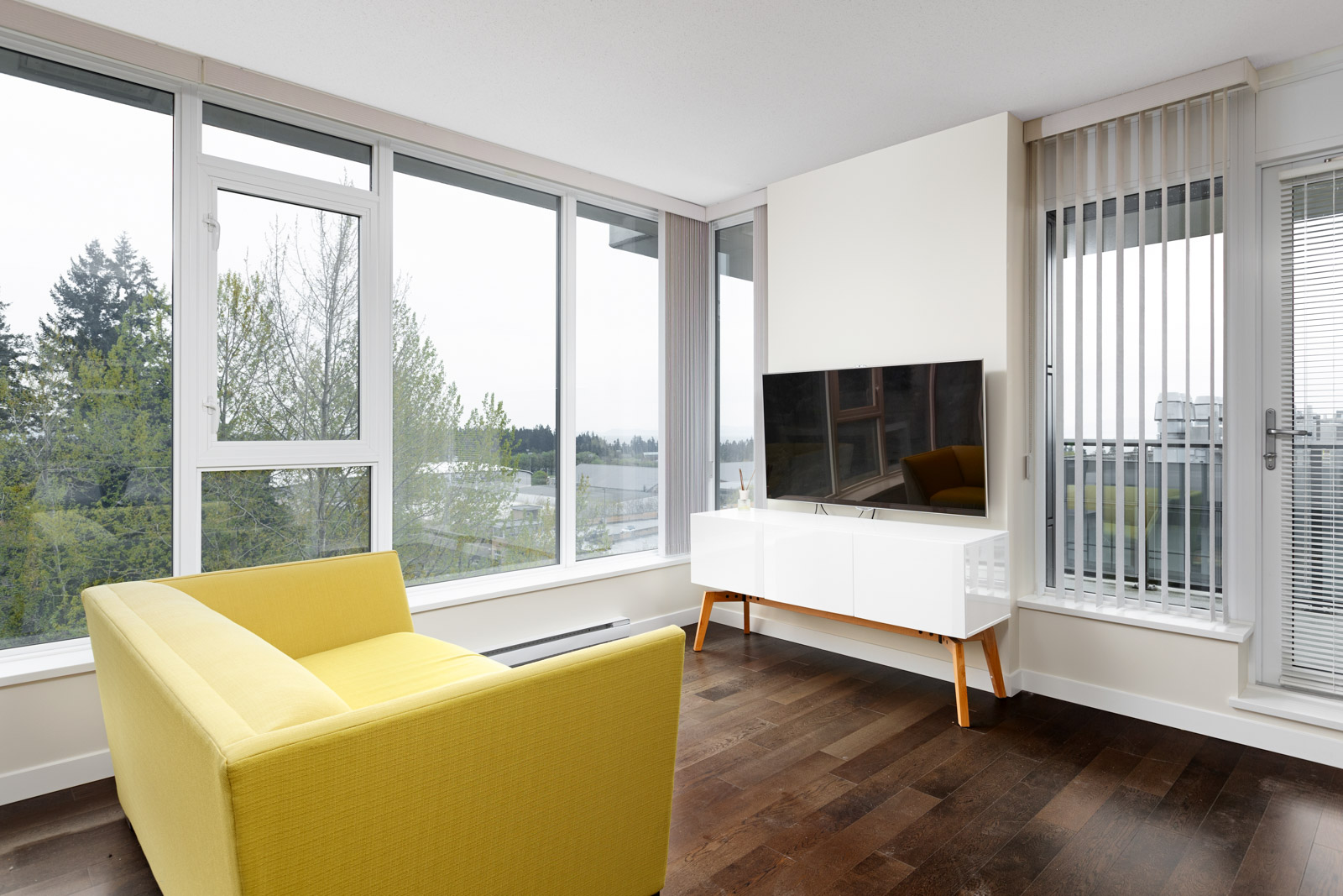 Living area featuring tv and yellow couch with view in UBC rental condo in Vancouver.