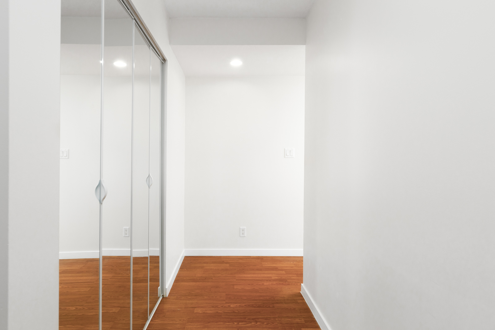 Interior hall with mirrored sliding closet inside Downtown Vancouver rental condo.
