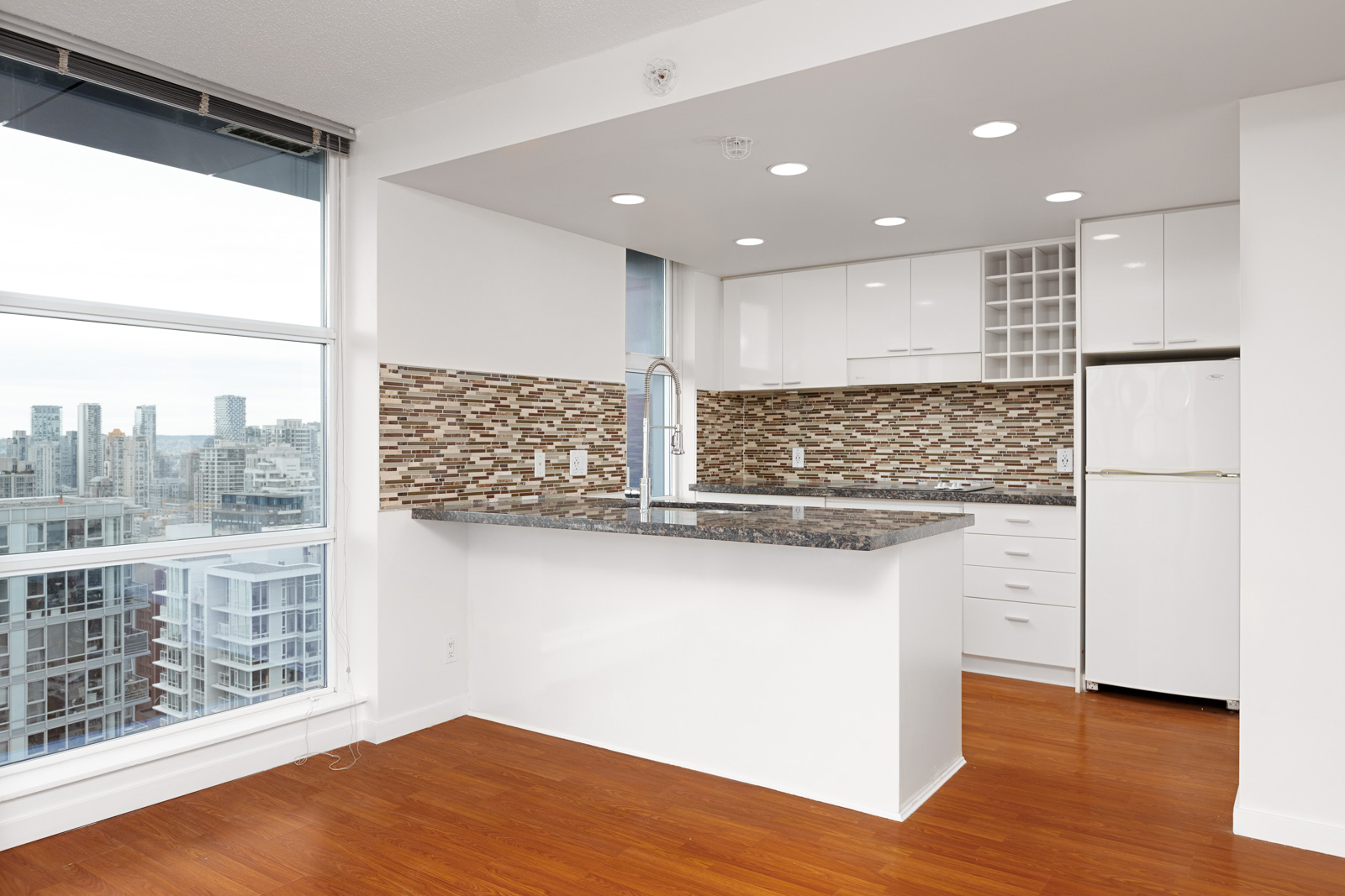 Kitchen with white cabinetry inside Downtown Vancouver rental condo.