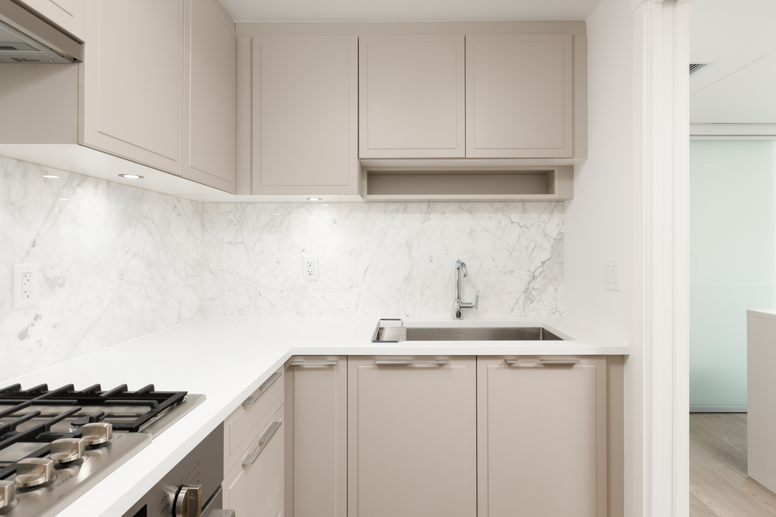 Kitchen area with beige cabinetry inside Vancouver townhome located in the Marpole community.
