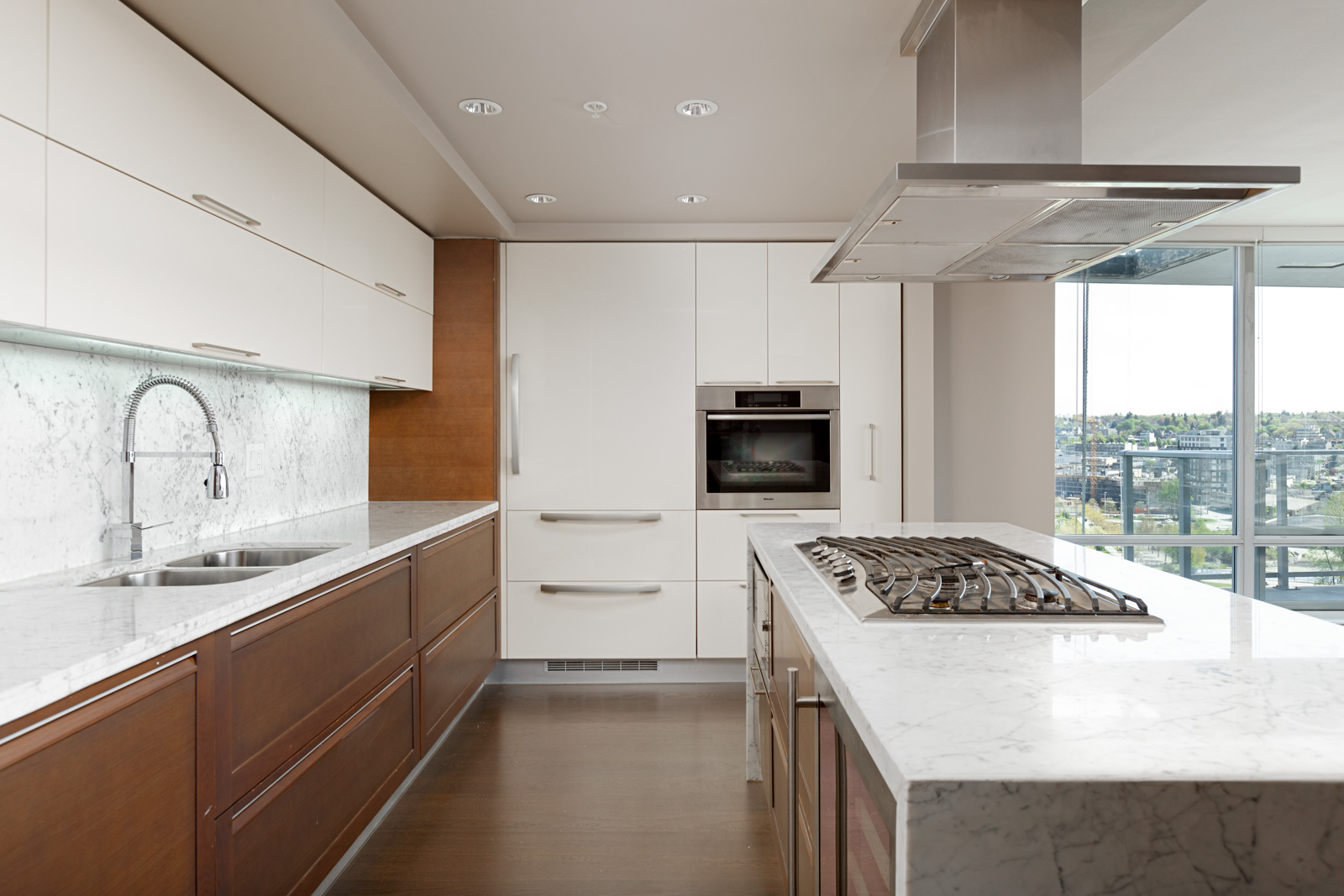 Kitchen with stainless steel appliances and marble counter top inside luxury Vancouver condo.