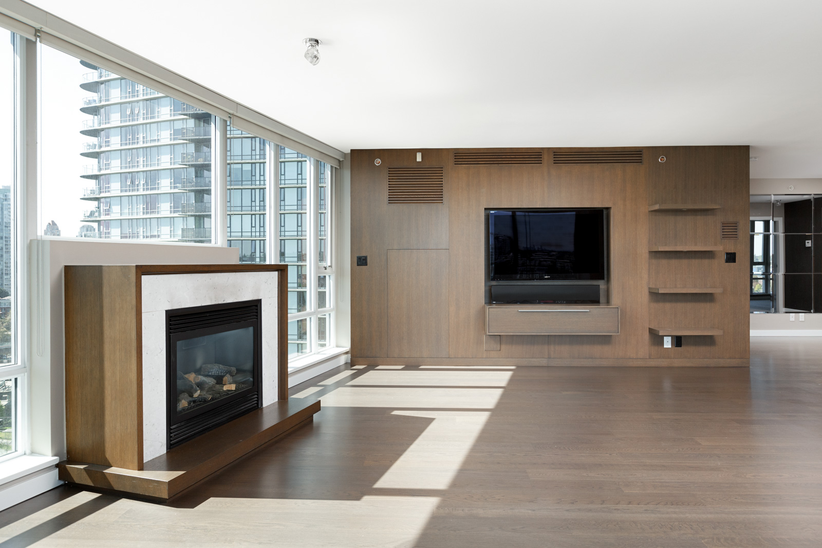 TV room in Vancouver rental condo with fireplace and floor-to-ceiling windows overlooking Vancouver city skyline.