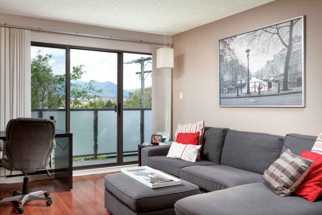 Living room with access to private balcony overlooking Vancouver.