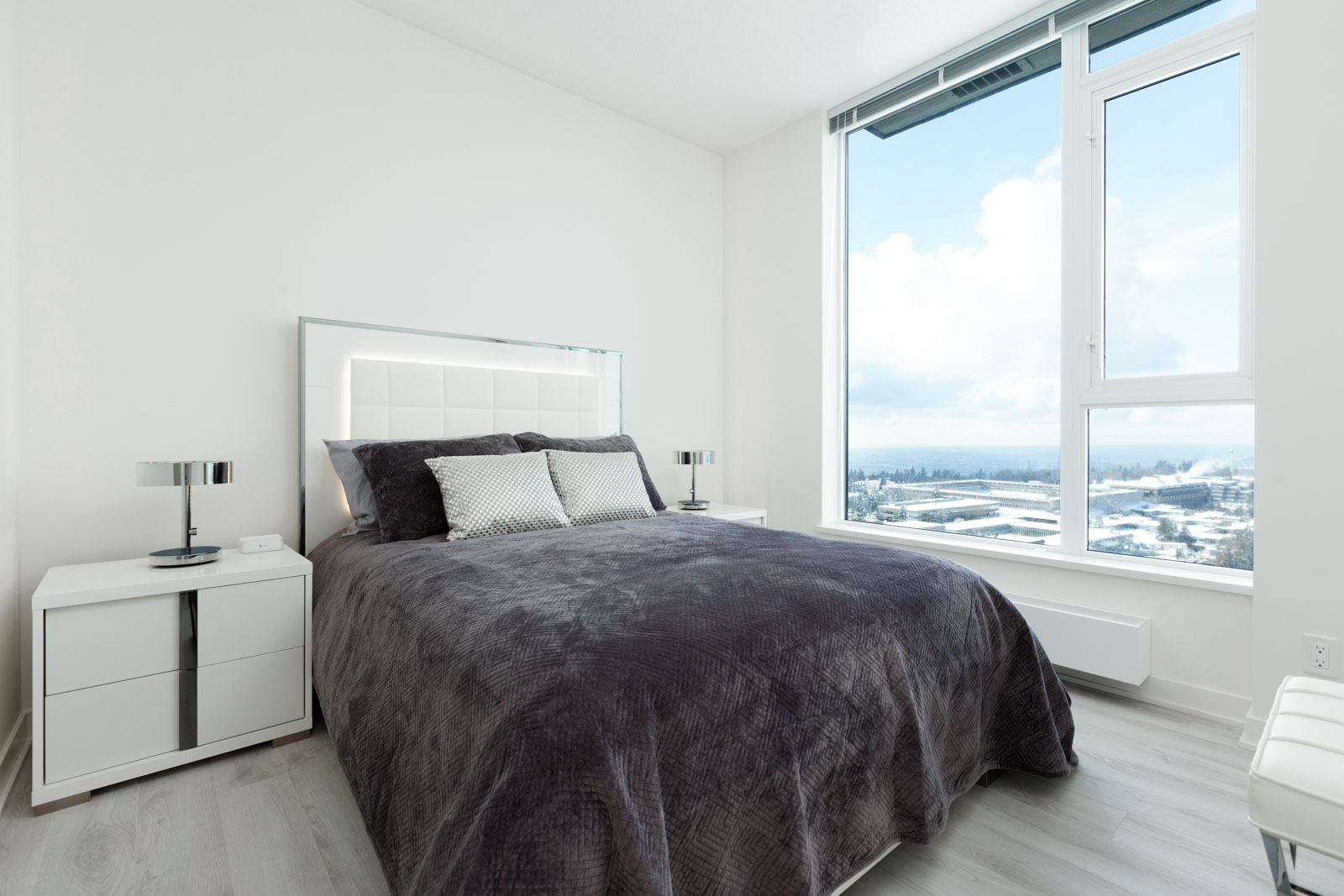 Bedroom inside luxury rental penthouse with views of Burnaby waterfront.