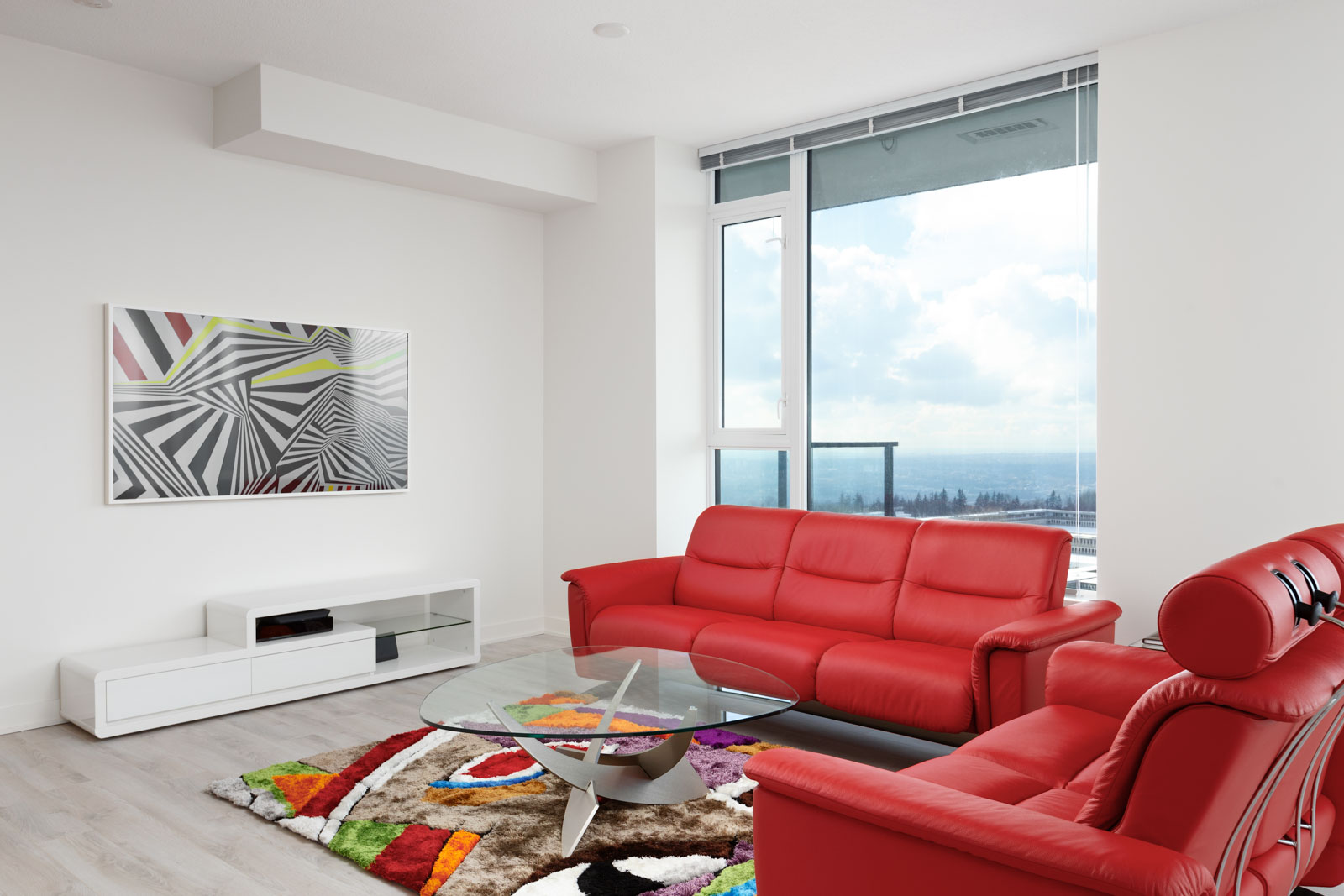 Living area with vibrant red couches and a bay window offering waterfront views from Burnaby rental penthouse.