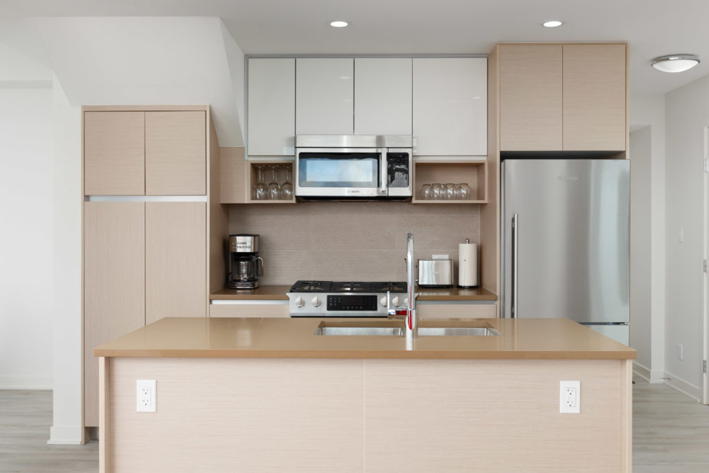 Kitchen with stainless steel appliances inside luxury Burnaby Mountain rental penthouse.