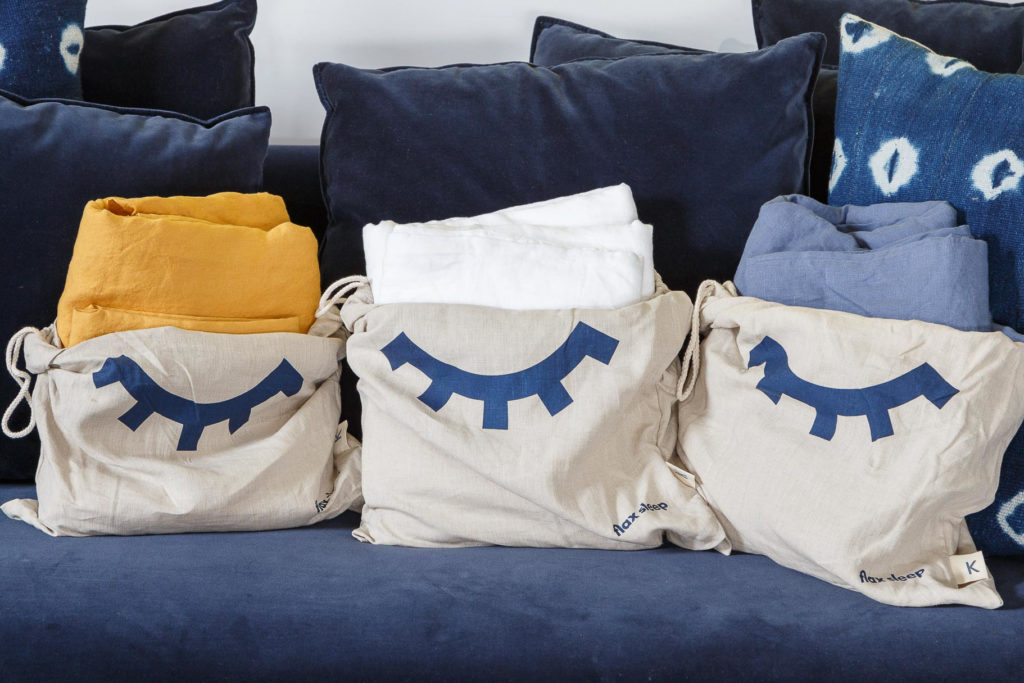 Flax Sleep bedding in linen bags and blue velvet pillows in background
