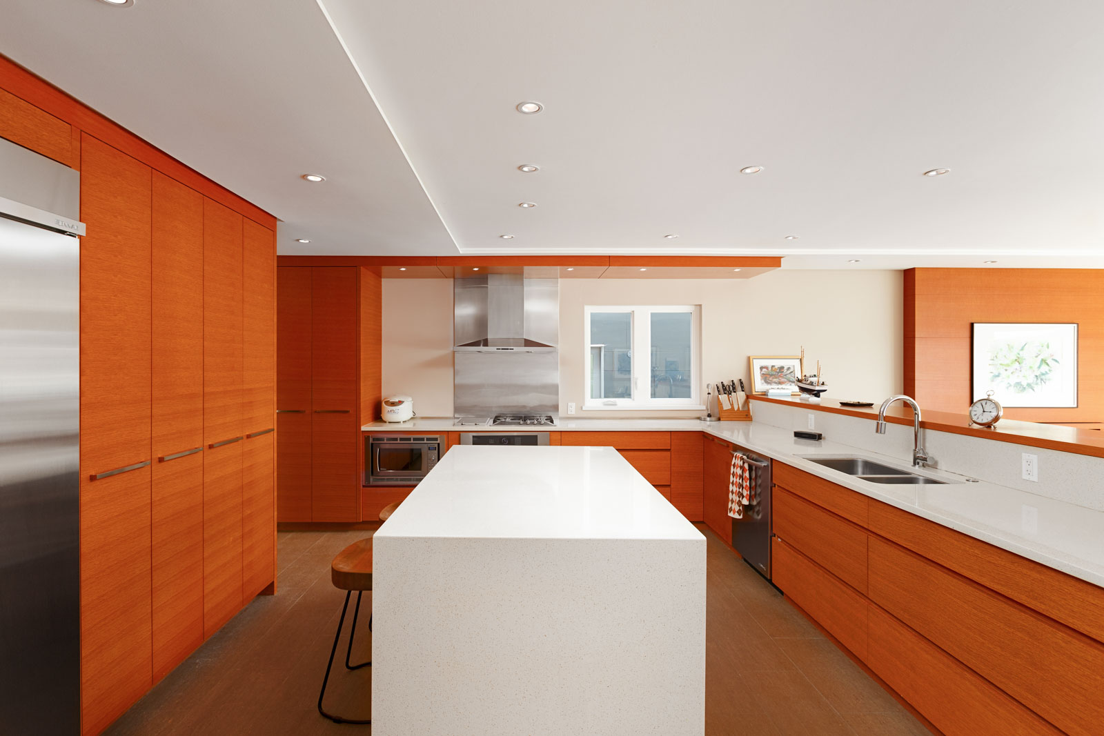 Kitchen with cherry wood cabinetry and a white island inside North Vancouver luxury rental.
