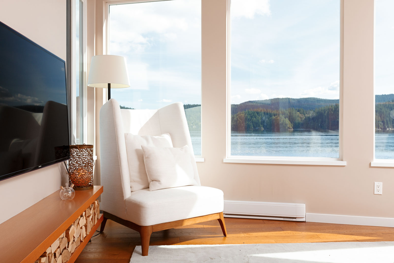 White chaise overlooking waterfront views from North Vancouver luxury rental.