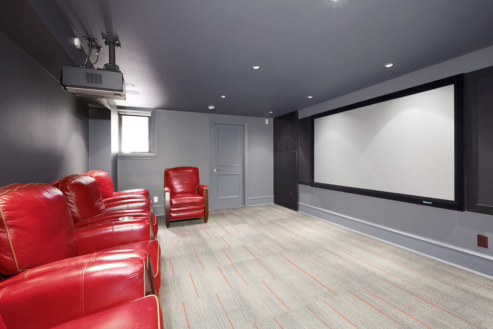 Theater room with red sofa chairs inside Vancouver luxury rental home.
