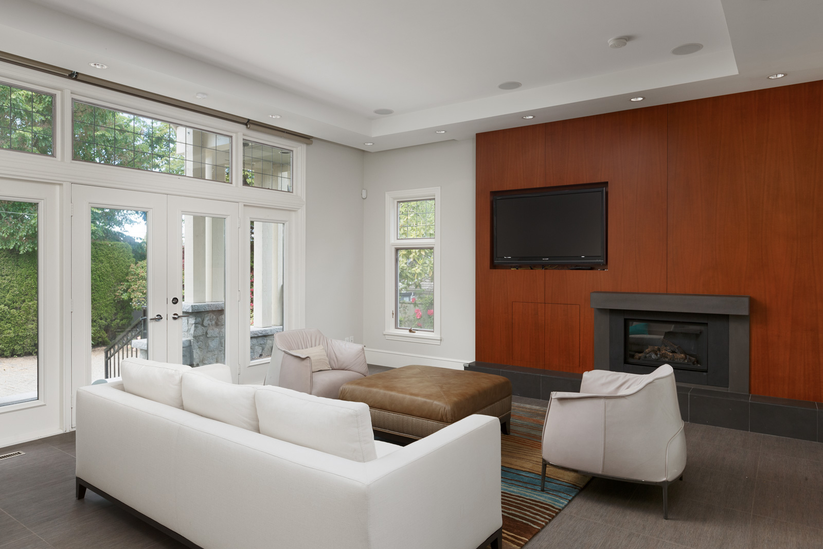 TV room with white couches and a fireplace inside Vancouver luxury rental.