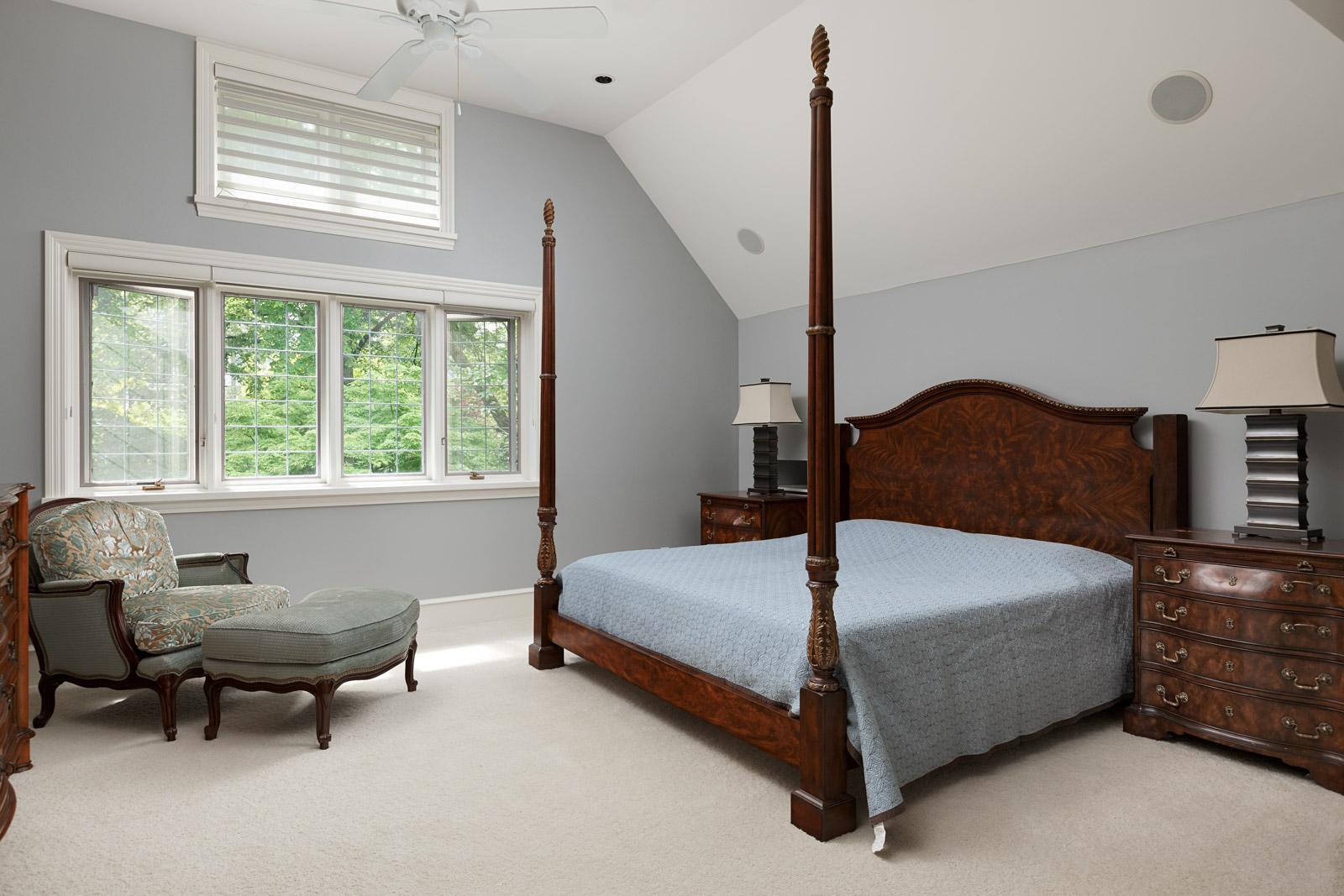 Bedroom with dark wood headrest inside Vancouver luxury rental home.