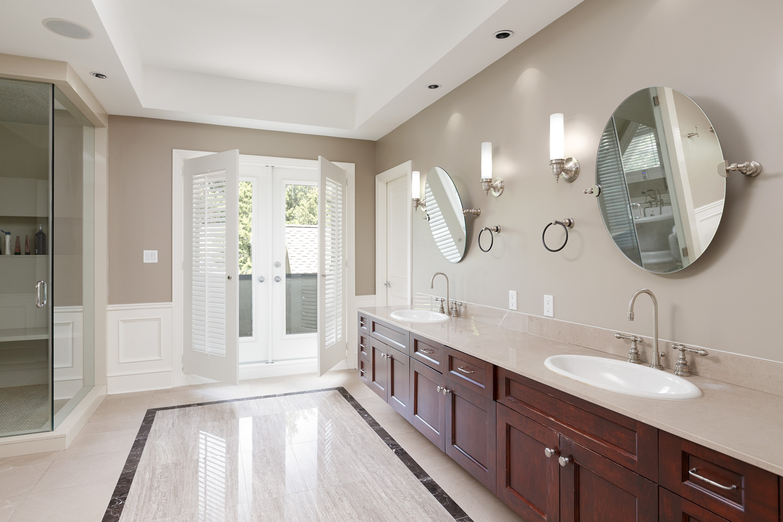 Bathroom with two sinks and French doors inside Vancouver luxury rental home.