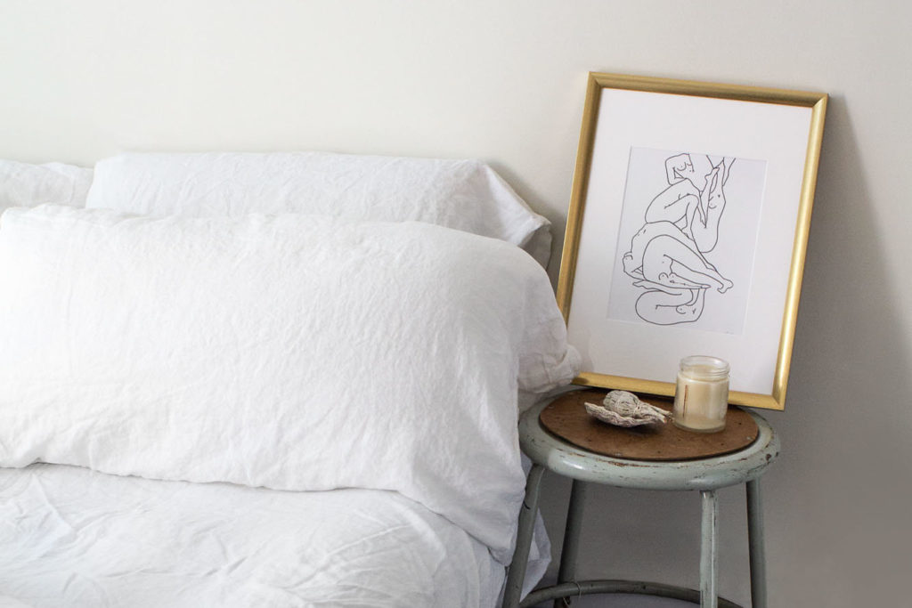White Flax Sleep bedding with black and white illustration in frame beside bed