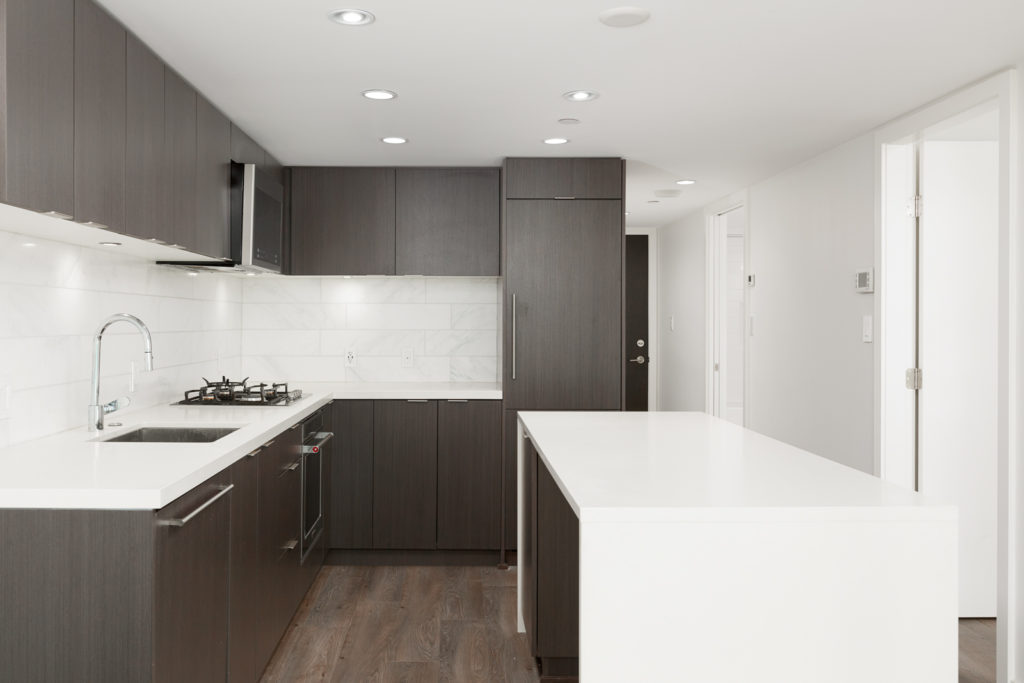 Kitchen with contrasting light and dark cabinetry inside Vancouver rental condo.