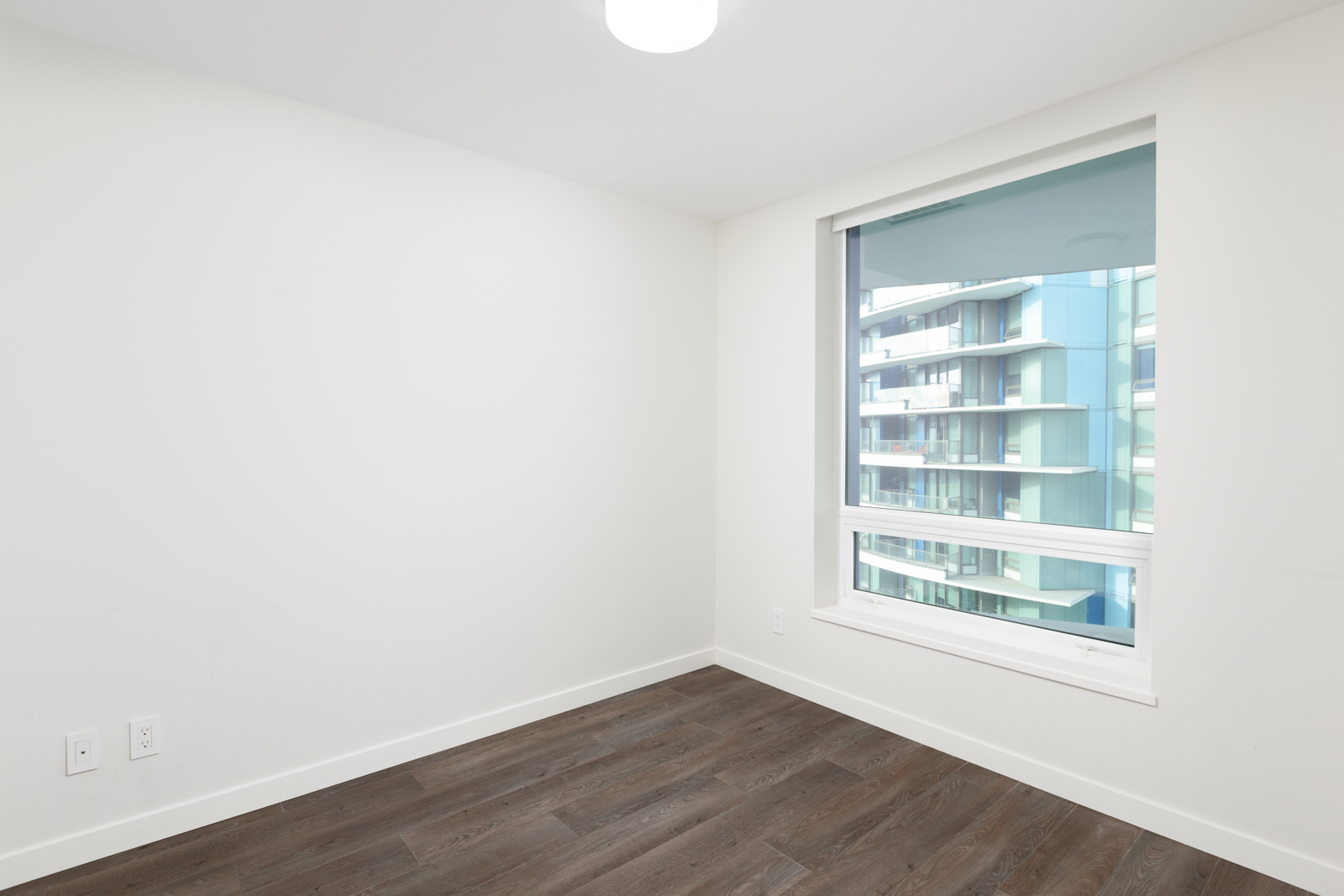 Bedroom with dark hardwood flooring inside luxury Downtown Vancouver condo.
