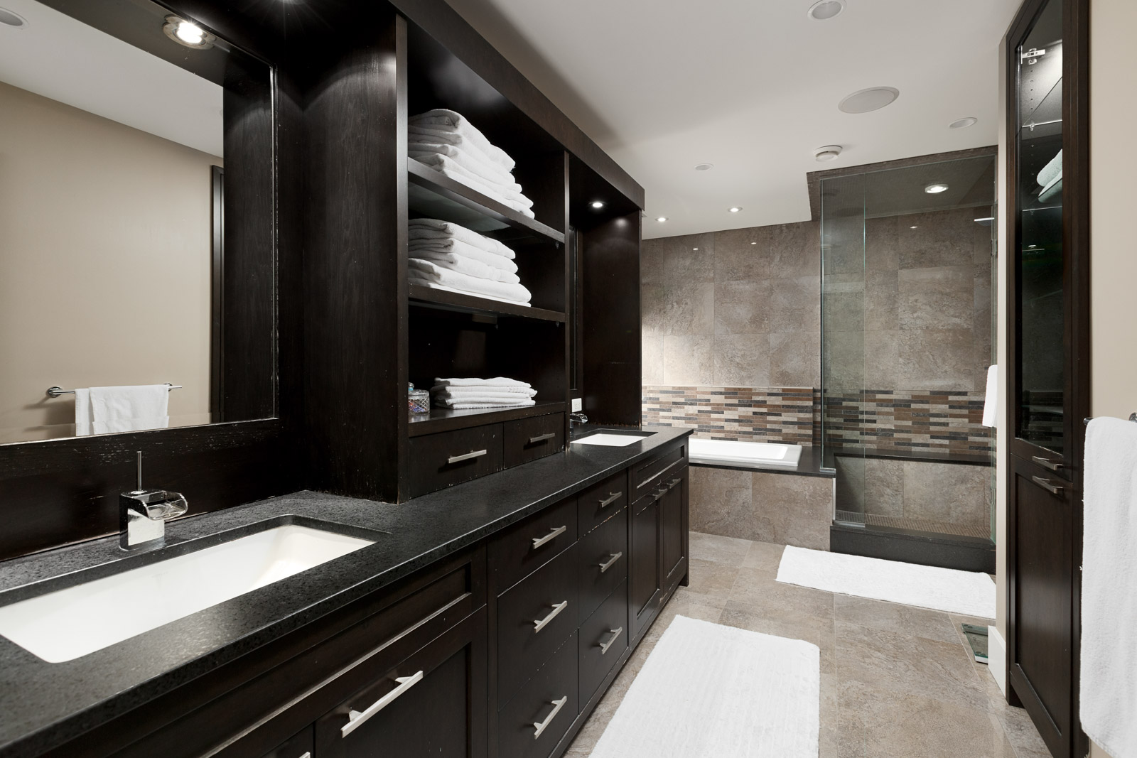 Bathroom with dark wood cabinetry and black counter tops inside North Vancouver luxury rental.