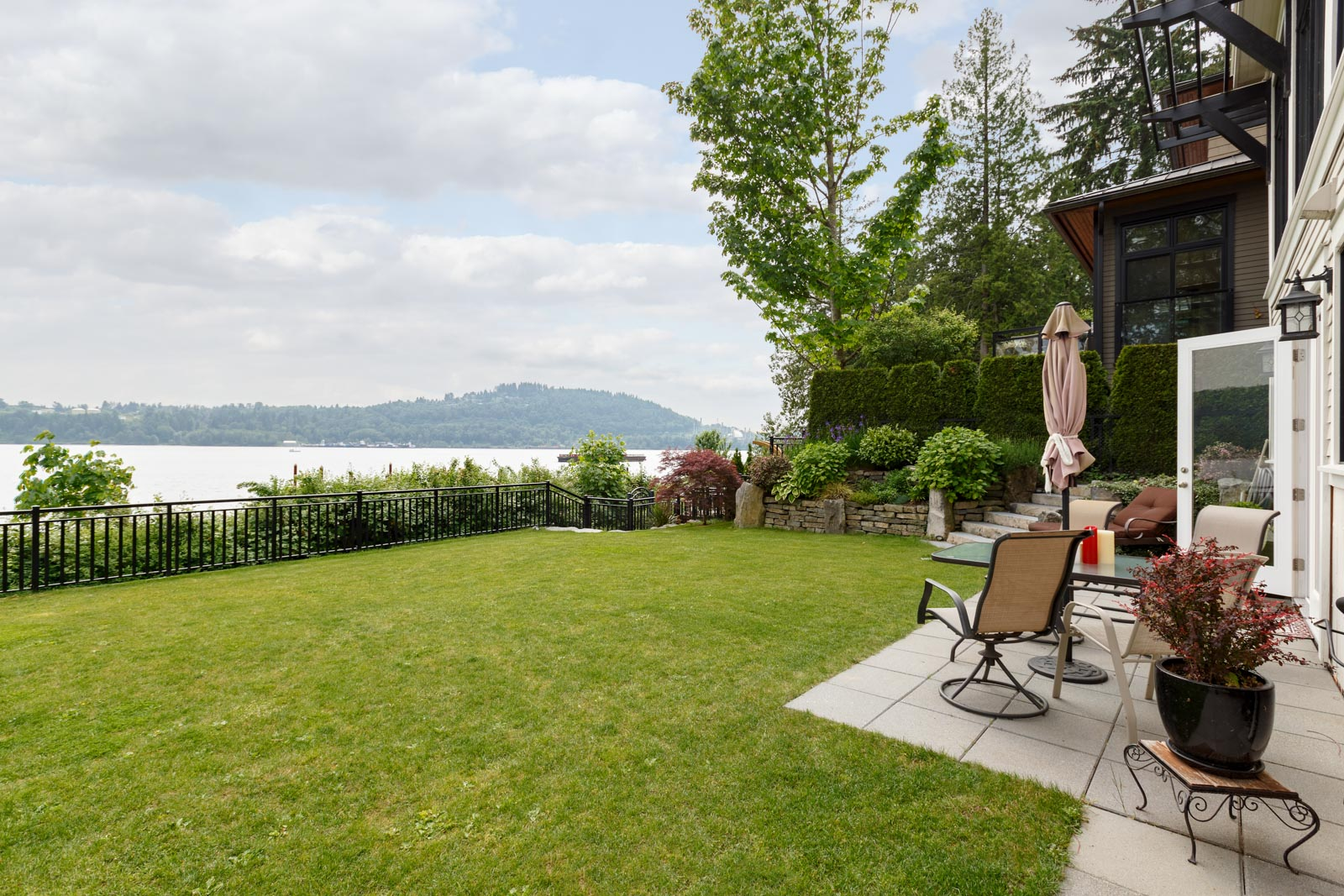 Yard outside North Vancouver luxury rental with view of the water.