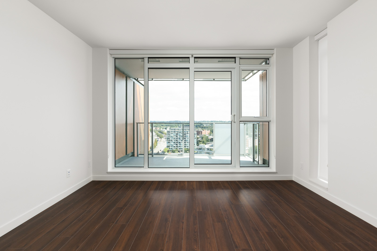Bedroom with floor-to-ceiling window and balcony access to views of Vancouver.