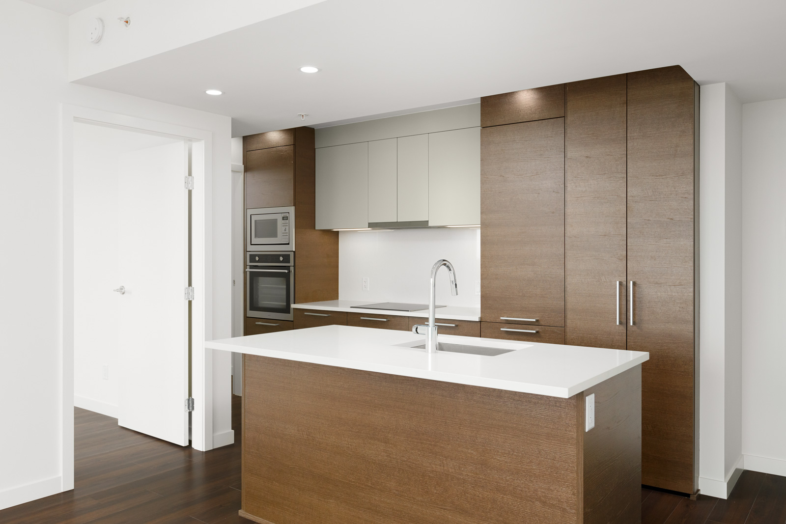 Kitchen with hardwood and white cabinetry inside Vancouver rental condo.