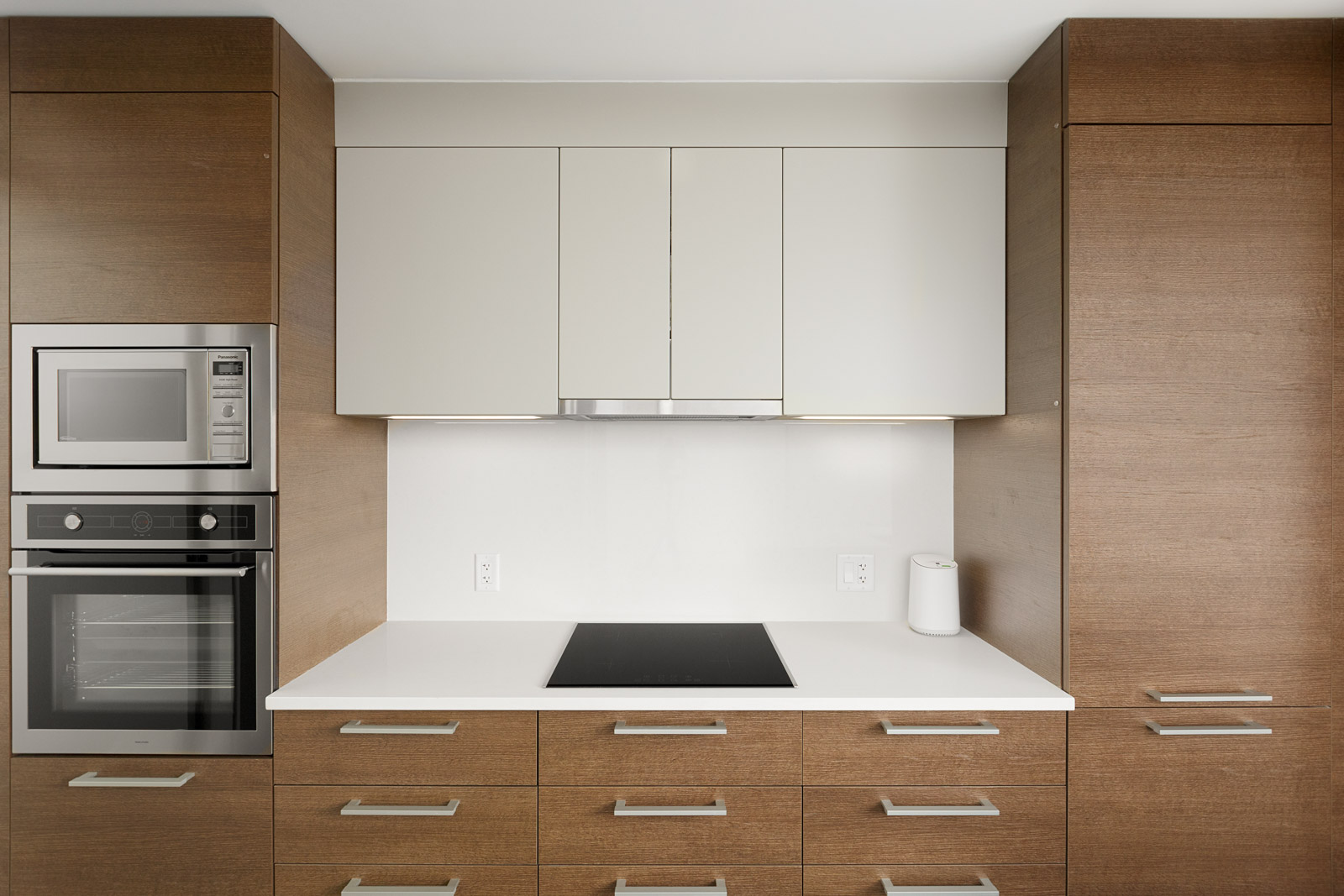 White and hardwood cabinetry inside the kitchen of a Mount Pleasant rental condo in Vancouver.