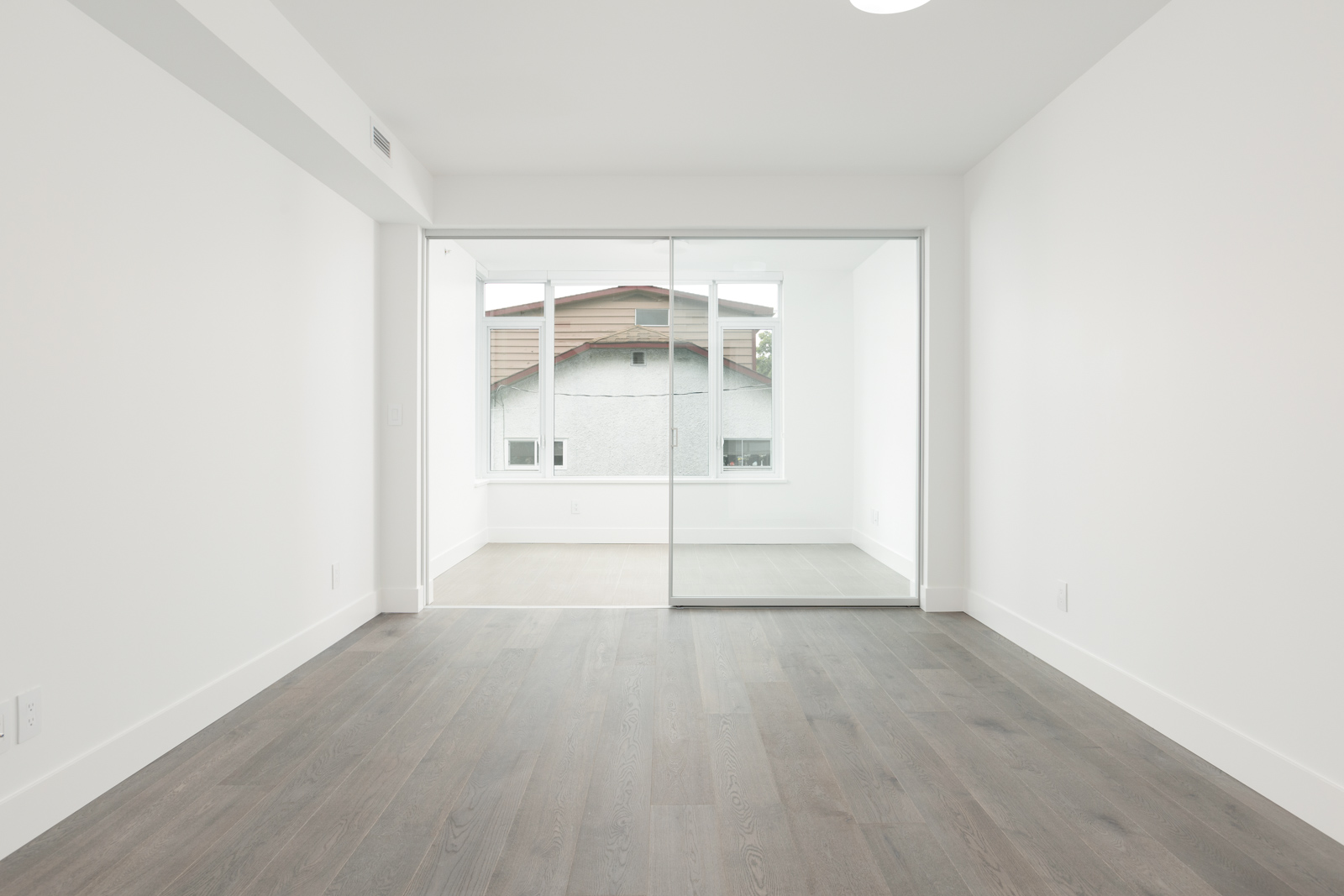 Empty room with ash hardwood and white walls inside Kerrisdale luxury condo.