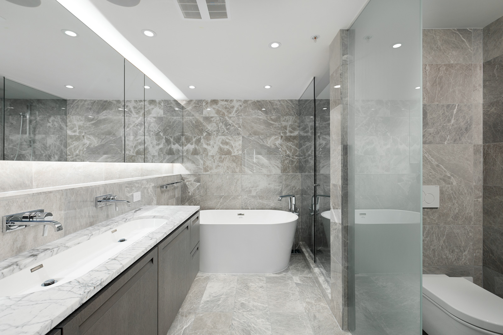 Bathroom with marbled grey tile inside luxury Vancouver rental.