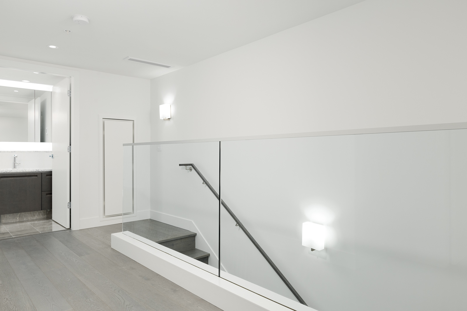 Stairwell with glass railing inside luxury Vancouver rental.
