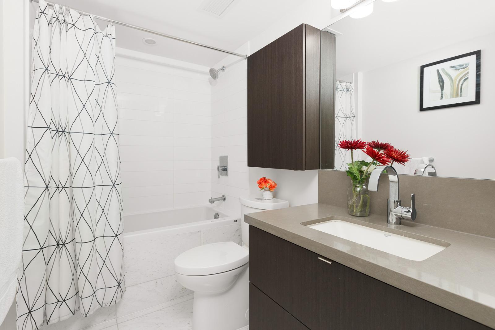 Bathroom with dark wood cabinetry inside luxury Vancouver rental.