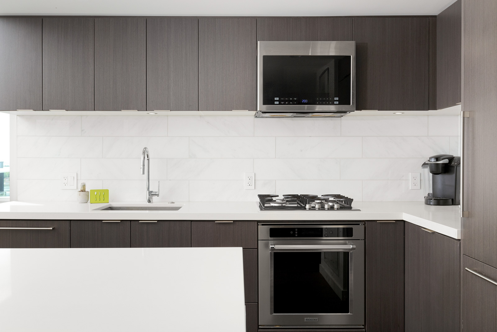 Kitchen with dark wood cabinetry and white counter top inside Vancouver luxury rental.